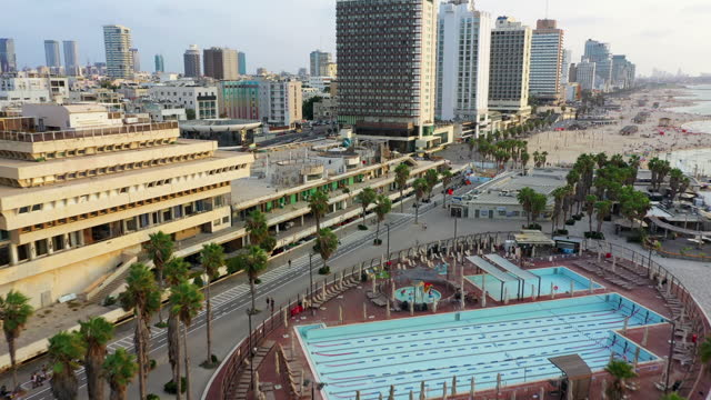 aerial shot of people at beach by hotels in city against sky, drone descending forward over harbor - tel aviv, israel - getting away from it all stock videos & royalty-free footage