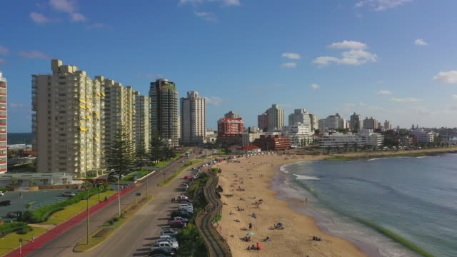aerial shot of people at beach by street in city on sunny day, drone flying forward towards buildings against sky - punta del este, uruguay - uruguay stock-videos und b-roll-filmmaterial