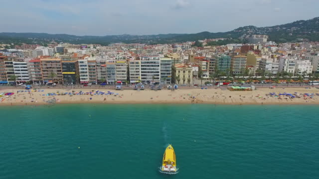 vidéos et rushes de aerial shot of people at beach in city against sky, drone ascending backward from buildings - lloret de mar, spain - mar