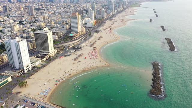 aerial shot of people at beach with groynes in modern city, drone descending over cityscape - tel aviv, israel - テルアビブ点の映像素材/bロール
