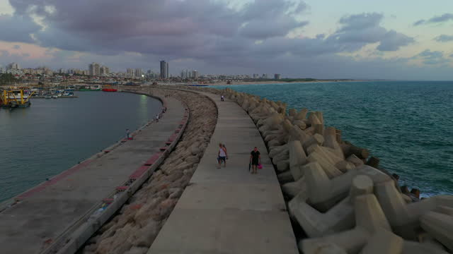 aerial shot of people at groyne by beautiful sea against sky during sunset, drone flying backward over walkway - ashdod, israel - coastal feature stock videos & royalty-free footage