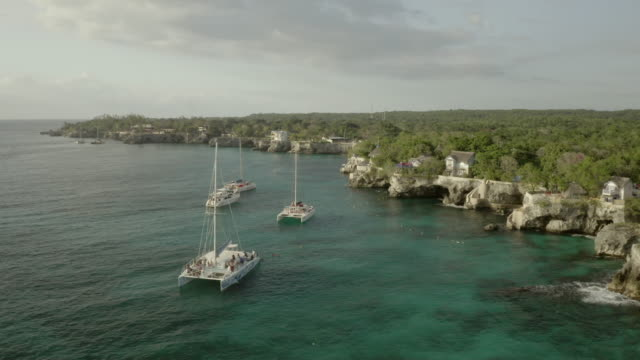 stockvideo's en b-roll-footage met aerial shot of people on catamarans in sea against cloudy sky, drone moving over boats during sunset - montego bay, jamaica - jamaica