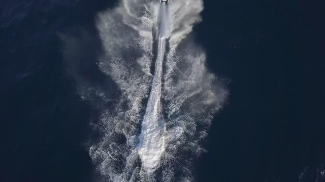aerial shot of person on jet ski splashing water in sea, drone flying forward over tourist enjoying aquatic sport - bandos, maldives - acquascooter video stock e b–roll