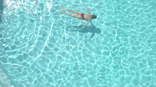 vidéos et rushes de aerial shot of person swimming in a pool - maillot une pièce