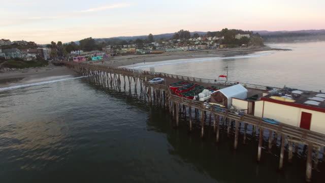 aerial shot of pier in sea against sky during sunset, drone moving forward towards city - santa cruz, california - カリフォルニア州サンタクルーズ点の映像素材/bロール