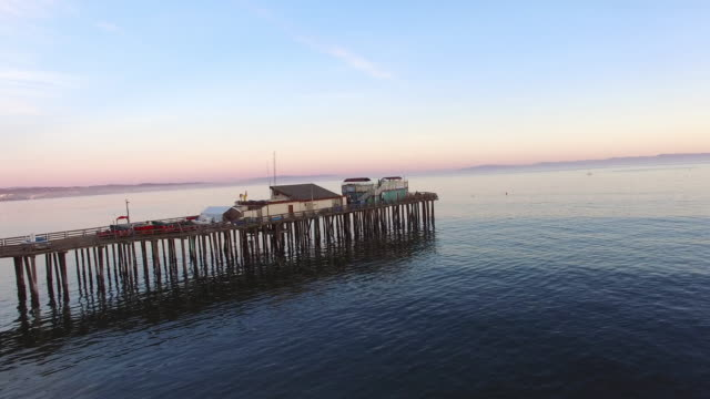aerial shot of pier in sea against sky during sunset, drone panning from left to right over water - santa cruz, california - カリフォルニア州サンタクルーズ点の映像素材/bロール