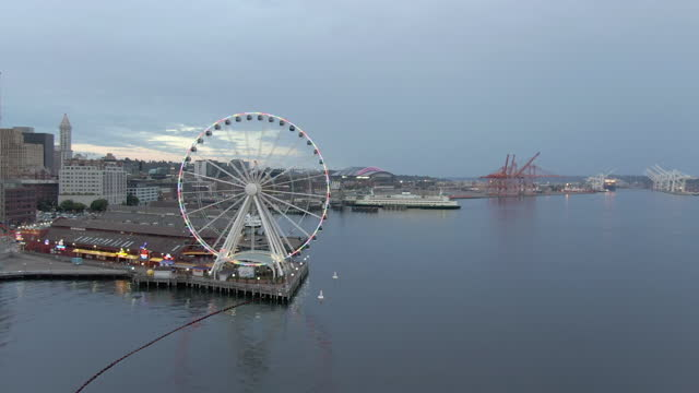 aerial shot of piers on elliot bay in city against sky at dusk, drone flying forward towards the seattle great wheel - pier stock videos & royalty-free footage