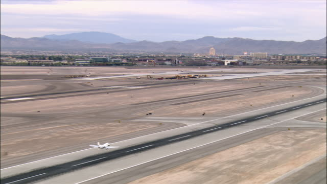 aerial shot of plane taking off at mccarran international airport and flying over mountains outside las vegas, nevada - runway stock videos & royalty-free footage
