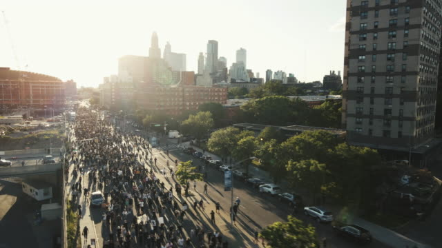 vidéos et rushes de aerial shot of protesters marching through the streets of brooklyn, new york city. shot at dusk near barclays center in 4k. - résolution 4k