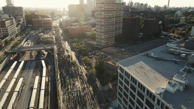 aerial shot of protesters marching through the streets of brooklyn, new york city. shot at dusk near barclays center in 4k. - organisation stock videos & royalty-free footage