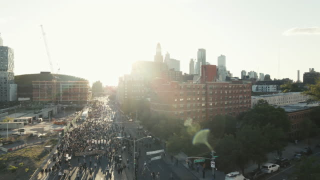 aerial shot of protesters marching through the streets of brooklyn, new york city. shot at dusk near barclays center in 4k. - social justice concept stock videos & royalty-free footage