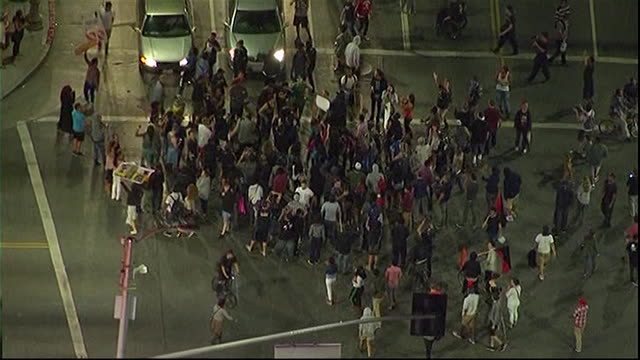 aerial shot of protesters on the streets of los angeles demonstrating after george zimmerman is acquitted for the murder of trayvon martin - crime or recreational drug or prison or legal trial stock-videos und b-roll-filmmaterial