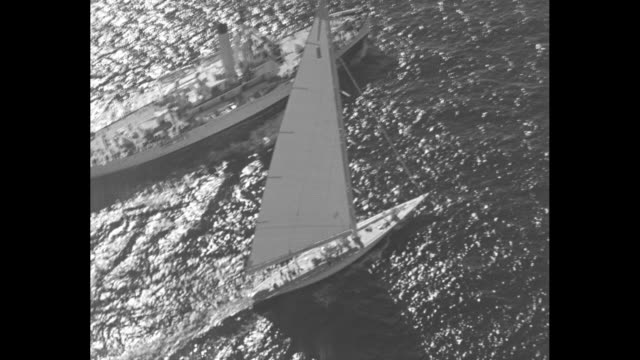 aerial shot of racing yacht rainbow sailing / crew sits on deck of rainbow while harold s vanderbilt steers helm / ship passes by rainbow / crew... - sailor suit stock videos and b-roll footage