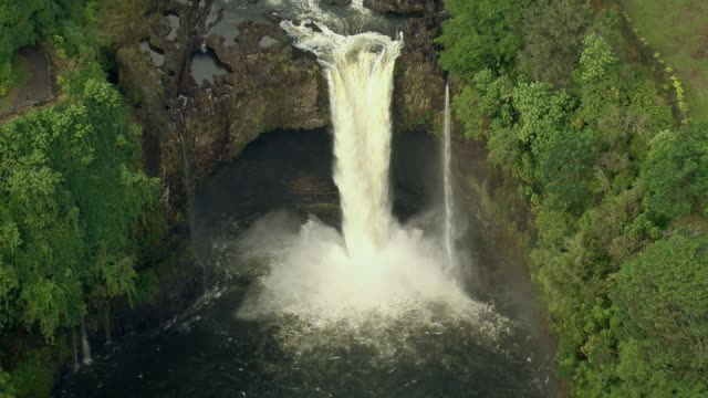 vídeos de stock, filmes e b-roll de aerial shot of rainbow falls plunging from the wailuku river into a pool below. the waterfall, also known as waianuenue, is located in the wailuku state park in hilo on the big island of hawaii. - polinésia