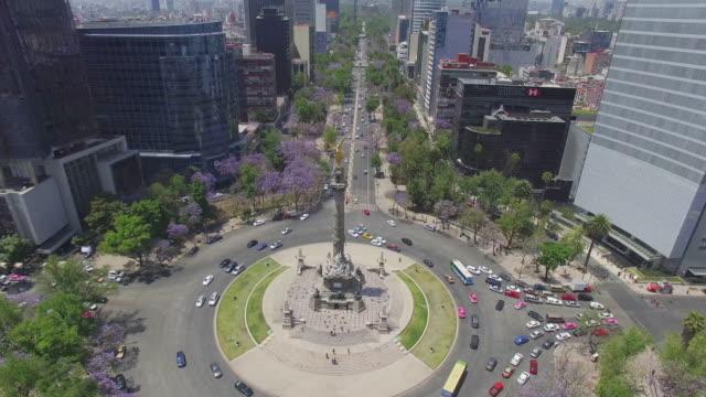 vídeos de stock, filmes e b-roll de aerial shot of reforma avenue and the angel de la independencia with lots of purple flowers - monumento da independência paseo de la reforma