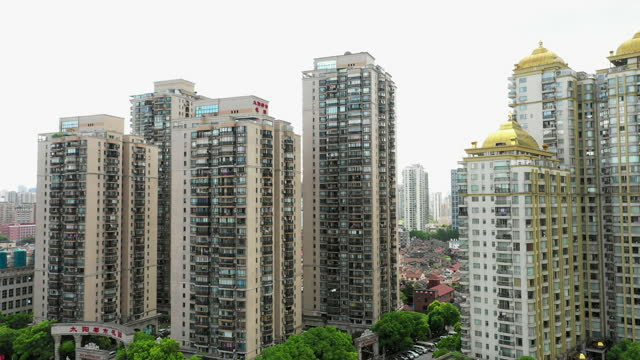 aerial shot of residential buildings in city against sky, drone flying forward towards structures - shanghai, china - housing development stock videos & royalty-free footage
