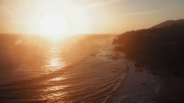 aerial shot of rippling waves and bright setting sun near el matador beach, malibu, califronia, usa - malibu stock videos & royalty-free footage