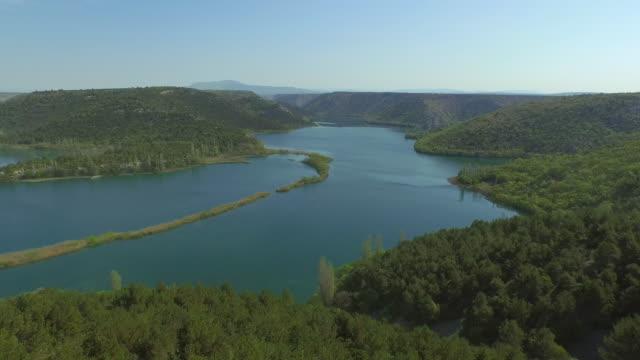 stockvideo's en b-roll-footage met aerial shot of river amidst green mountains against sky, drone is moving backwards - krka, croatia - achterstevoren