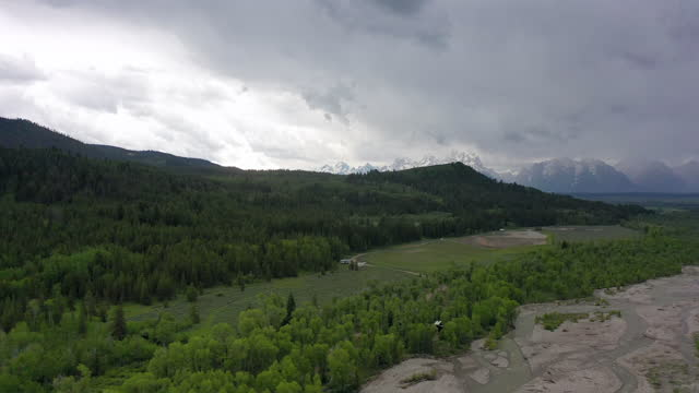 aerial shot of river and green forest against cloudy sky, drone flying forward towards mountains - grand teton national park, wyoming - grand teton national park stock videos & royalty-free footage