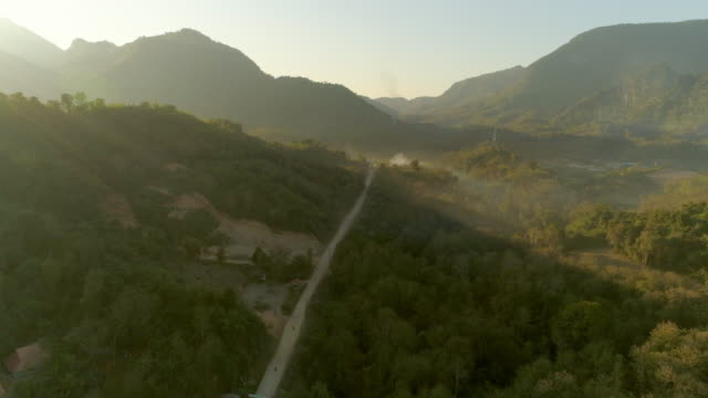 vidéos et rushes de aerial shot of road amidst green trees near village against sky, drone ascending over landscape during sunrise - tat sae waterfalls, laos - monter