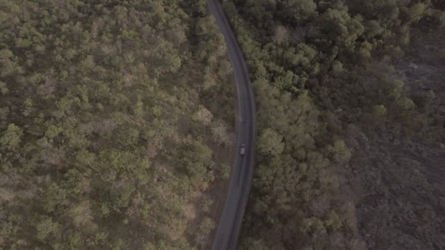aerial shot of road in the hill - dirt track stock videos and b-roll footage