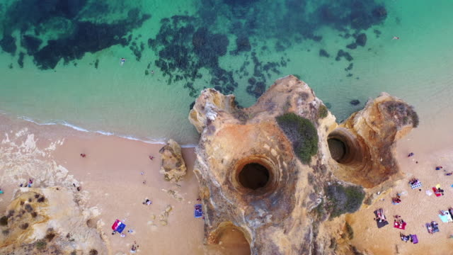 aerial shot of rock formation amidst people at beach, drone ascending over tourists on shore - lagos, portugal - algarve stock videos & royalty-free footage