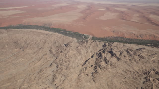 vídeos y material grabado en eventos de stock de aerial shot of rock formation and sand dunes in desert on sunny day, scenic view of trees and plants on arid landscape seen from airplane - sossusvlei, namibia - característica costera