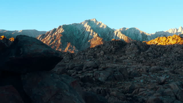 aerial shot of rocks at famous natural landmark against blue sky, drone flying forward towards rocky mountains on sunny day - alabama hills, california - natural landmark stock videos & royalty-free footage