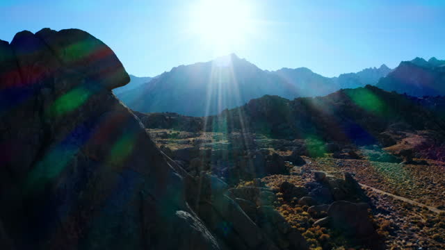 aerial shot of rocks at famous natural landmark against sky, drone flying backward from rocky mountains on sunny day - alabama hills, california - natural landmark stock videos & royalty-free footage