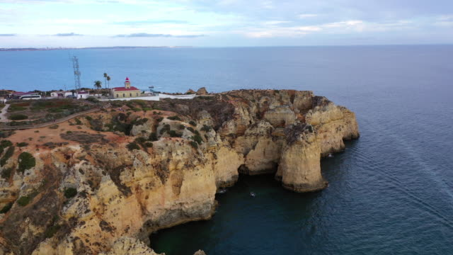 aerial shot of rocky cliffs in sea against cloudy sky, drone flying over rock formation - lagos, portugal - roccia video stock e b–roll