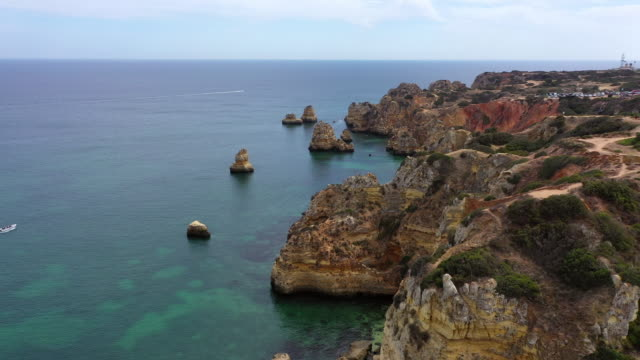 aerial shot of rocky cliffs in sea against sky on sunny day, drone flying forward over coastline - lagos, portugal - algarve stock videos & royalty-free footage