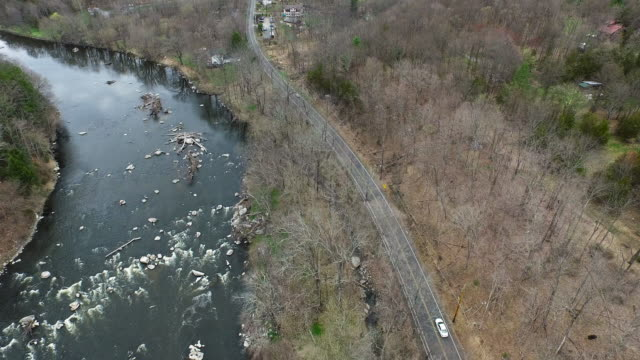 Aerial shot of rocky river and one-lane road winding parallel toward small town