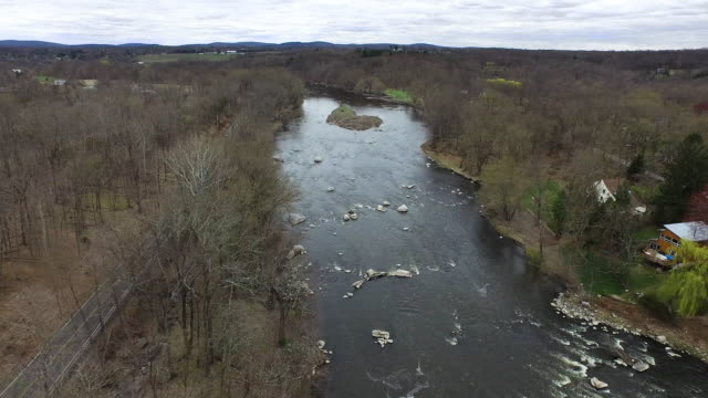 Aerial shot of rocky river with winter trees along both banks