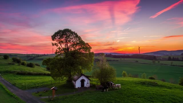 Aerial shot of rural landscape with chapel in the Eifel mountain range in Germany at sunset