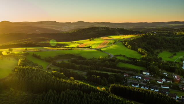 Aerial shot of rural landscape with misty hills in Germany