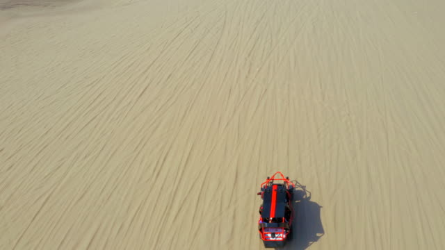 aerial shot of safari vehicle moving on sand in desert, drone following dune buggy - huacachina, peru - sand dune stock videos & royalty-free footage