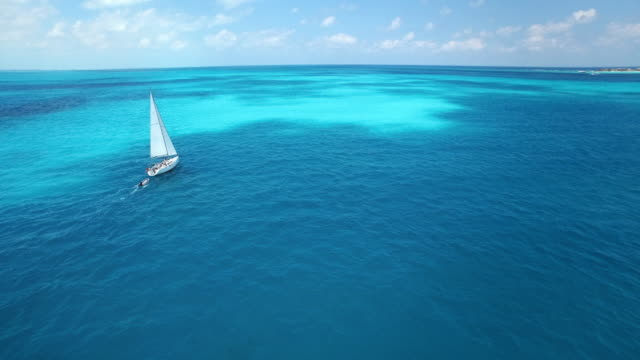 vídeos de stock, filmes e b-roll de aerial shot of sailboat sailing into the horizon on beautiful clear blue tropical ocean - transporte marítimo