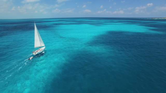 Aerial shot of sailboat sailing into the horizon on beautiful clear blue tropical ocean