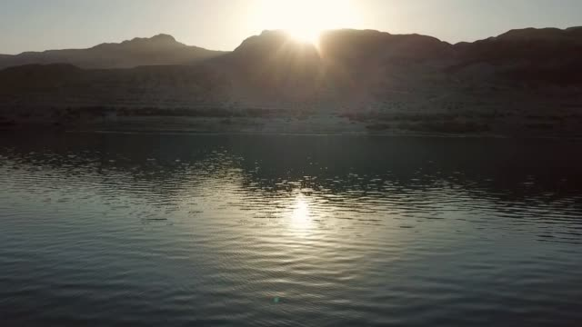 vidéos et rushes de aerial shot of salt lake near mountains against sky at sunset, drone ascending over famous natural landmark - dead sea, israel - natural landmark