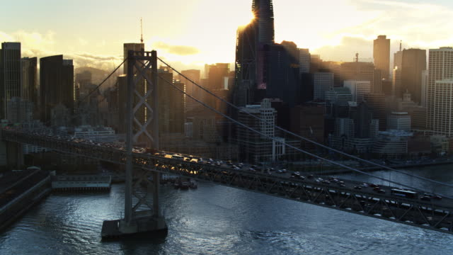 aerial shot of san francisco embarcadero and financial district behind the bay bridge - baia di san francisco video stock e b–roll
