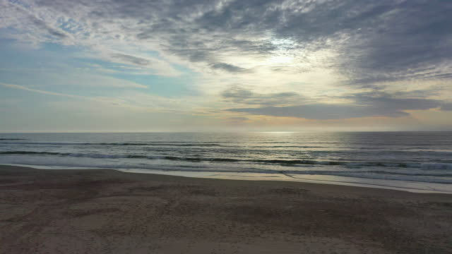 aerial shot of sea at beach against cloudy sky during sunset, drone flying forward towards splashing waves - punta del este, uruguay - the way forward stock videos & royalty-free footage