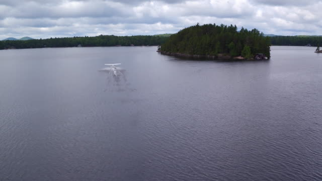 aerial shot of seaplane landing on a lake, afternoon - splashdown stock videos & royalty-free footage