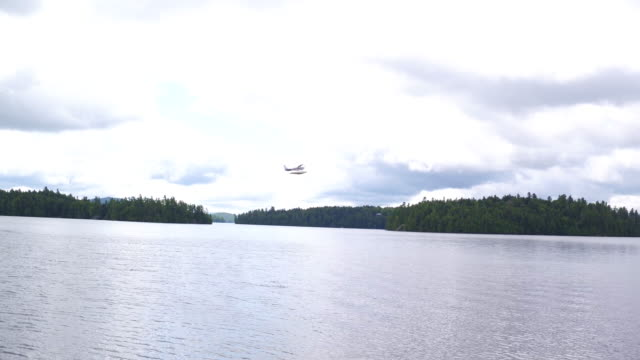 Aerial shot of seaplane taking off and flying over water, afternoon