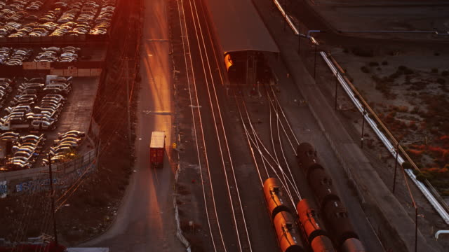 aerial shot of semi truck driving alongside freight train - 大型トレーラー点の映像素材/bロール