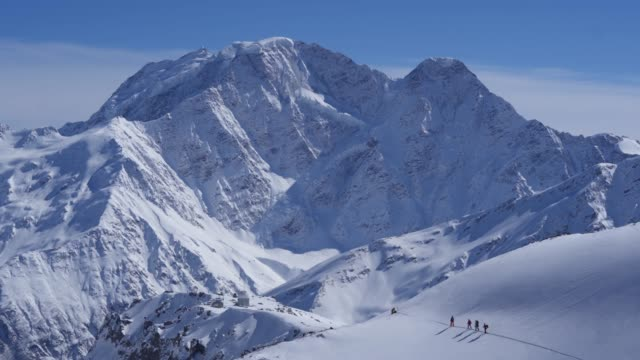 aerial shot of skiers hiking up a mountainside in the snow with glacier with mount elbrus behind - 4k resolution stock videos & royalty-free footage