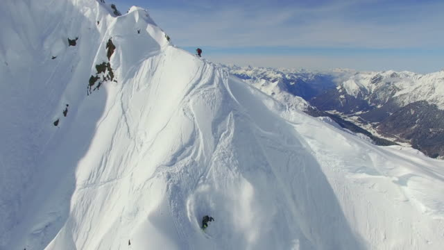 aerial shot of skiers skiing from the top of a mountain. - snowcapped mountain stock videos & royalty-free footage