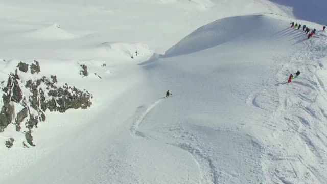 aerial shot of skiers skiing from the top of a mountain. - bastoncino da sci video stock e b–roll