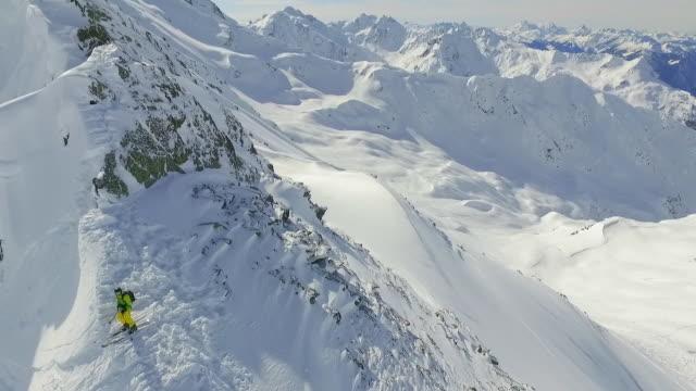 vídeos de stock e filmes b-roll de aerial shot of skiers skiing from the top of a mountain. - bastão de esqui