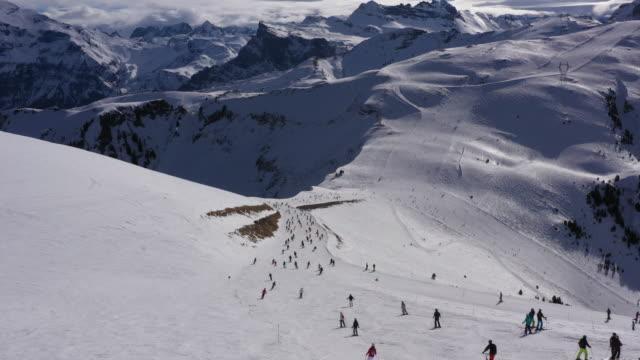 vídeos y material grabado en eventos de stock de toma aérea de esquiadores en los alpes franceses - centro de esquí