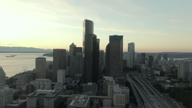 aerial shot of skyscrapers in downtown by dr jose p rizal bridge, drone flying forward over modern city by elliott bay against sky at sunset - seattle, washington - elliott bay stock videos & royalty-free footage